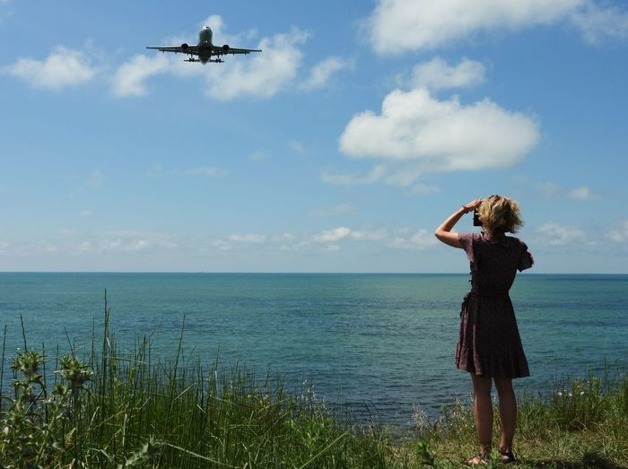 Woman standing in sea against sky and airplane