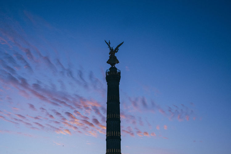 Low angle view of silhouette statue on column against sky during sunset