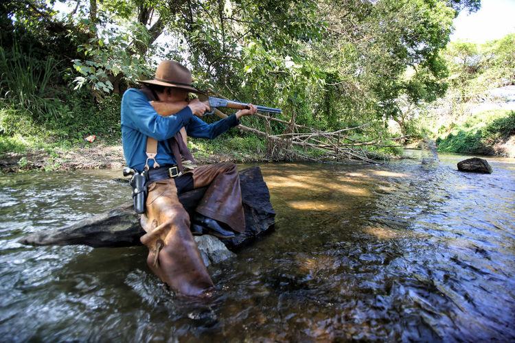 Man wearing costume aiming gun while sitting on rock in river