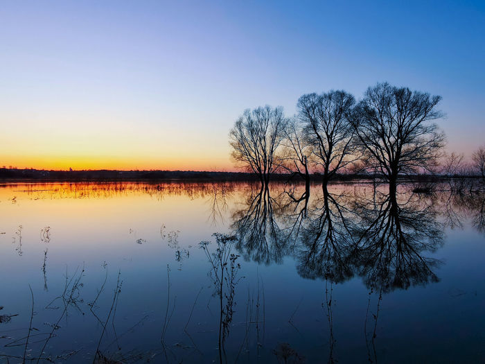 Scenic view of lake against sky during sunset