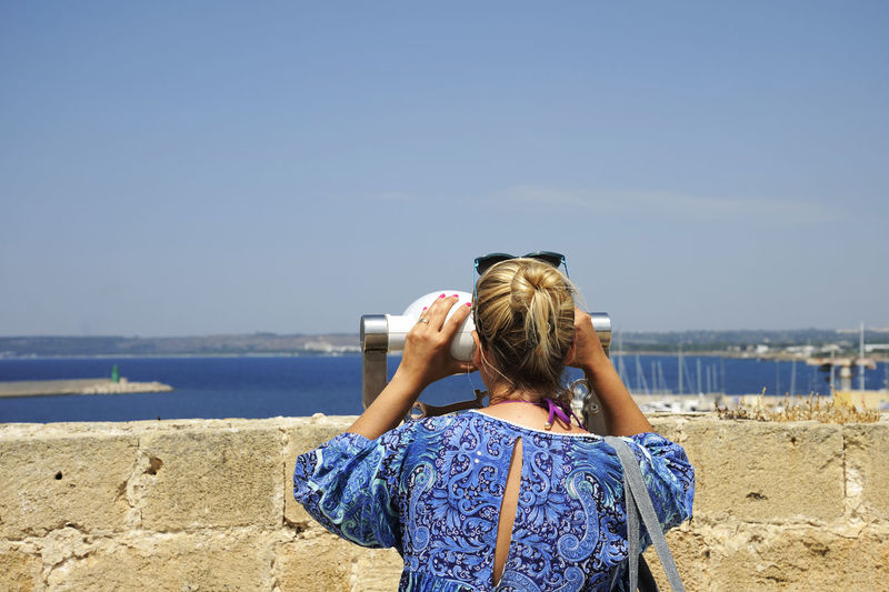 Rear view of woman looking sea through coin-operated binoculars