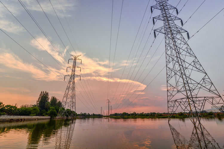 electricity pylons at sunset Electricity  Sky Fuel And Power Generation Power Line  Cable Electricity Pylon Technology Power Supply Connection Cloud - Sky Water Sunset Nature No People Plant Tree Beauty In Nature Outdoors Waterfront Complexity Electrical Equipment Telephone Line