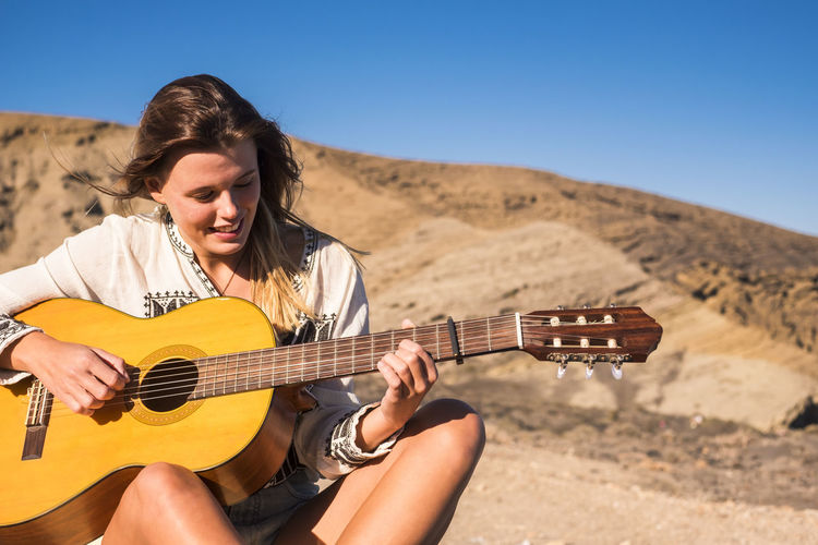 Young woman playing guitar against mountain