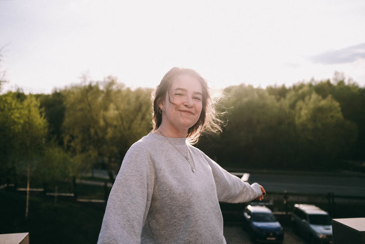 Portrait of smiling woman standing against trees
