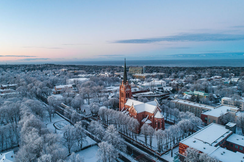 Wintertime Church Gothic Style Blue Building Exterior Architecture Built Structure Sky City High Angle View Cityscape Sunset Residential District Winter Building Nature Roof Cold Temperature Water Outdoors TOWNSCAPE No People Snow Scenics - Nature Morning Light Frozen Nature Church Tower Golden Sunrise Tranquility Lithuania Nature Aerial View Moody Sky