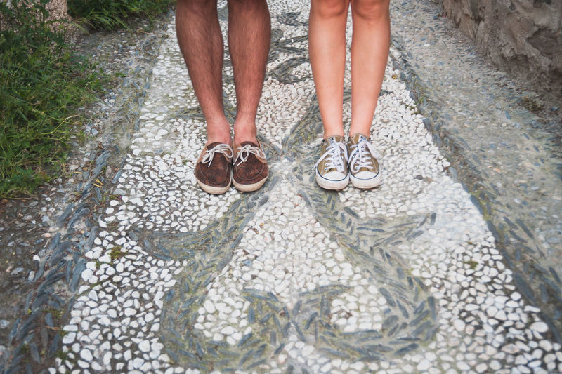 Low section of couple standing on mosaic footpath