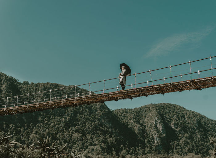 Low Angle View Of Young Woman Standing On Bridge By Mountains Against Sky