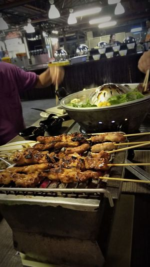 Charcoal Grill Thai Steamboat Thai Buffet Barbecue Chicken Satay Food Food And Drink Grilled Grilled Meat Skewers Hand Healthy Eating Incidental People Marinated Meat Meat Preparing Food Real People Restaurant Street Food Table Thai BBQ
