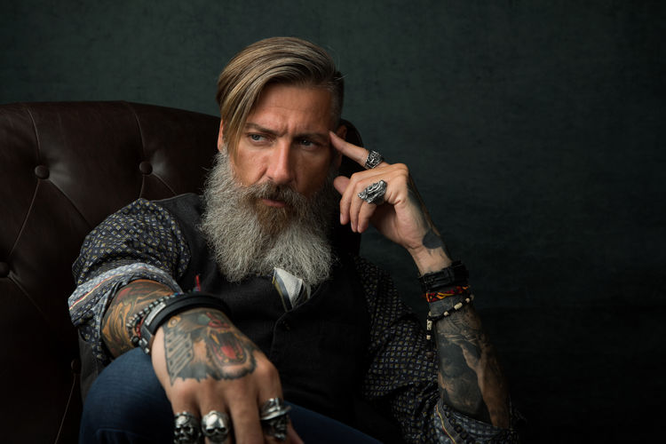 Bearded Man Sitting Against Black Background
