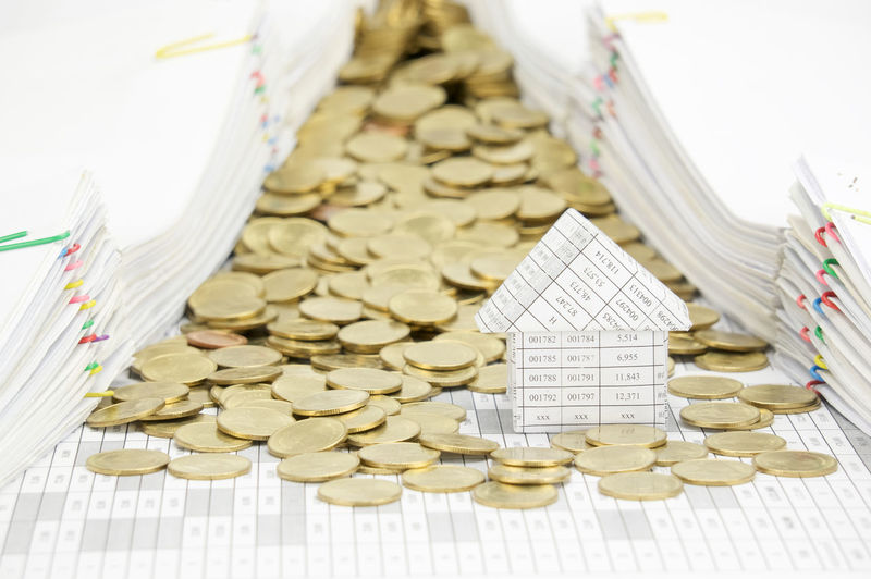 House with stack of gold coins on finance account have pile of document with colorful paperclip as background. Gold Home Planning Stack Work Account Balance Business Close-up Coin Currency Data Document Finance House Invest Money Paper Paperwork Pile Report Success Wealth White Workload