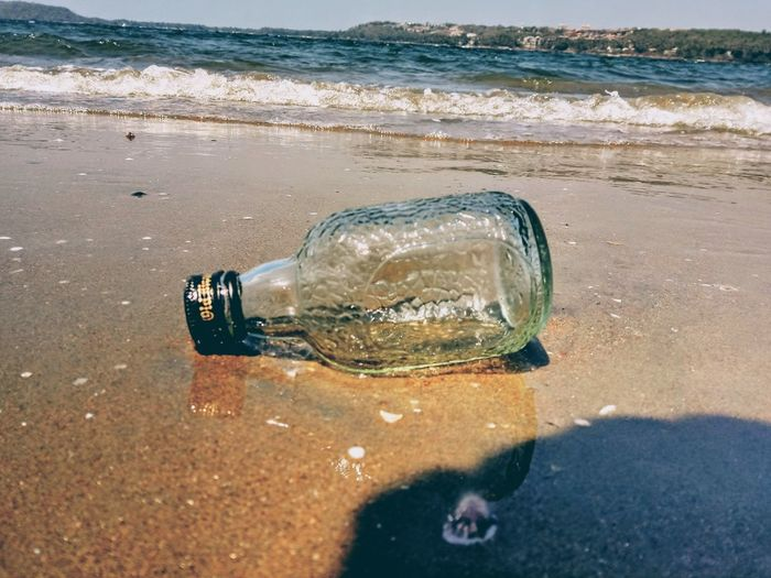 Close-up of drinking glass on beach
