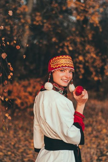 Portrait of smiling young woman wearing traditional clothing while standing in park during autumn