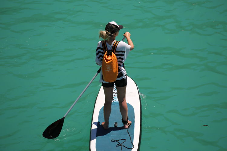 Full length rear view of woman paddleboarding in turquoise sea
