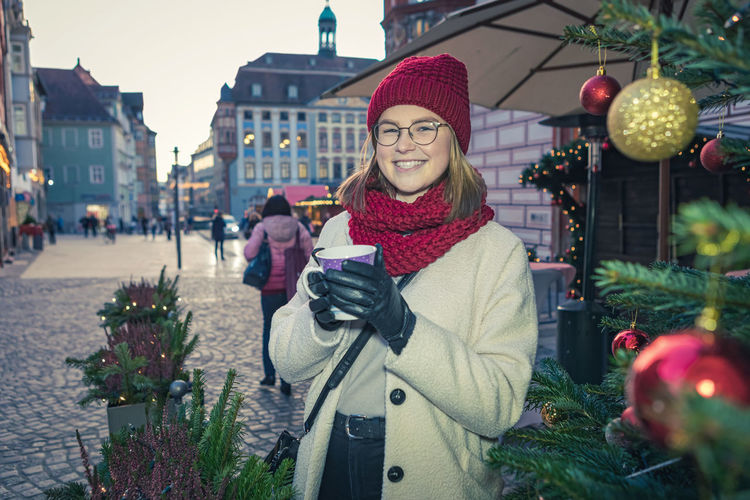 Portrait of smiling woman holding drink on street in city during christmas