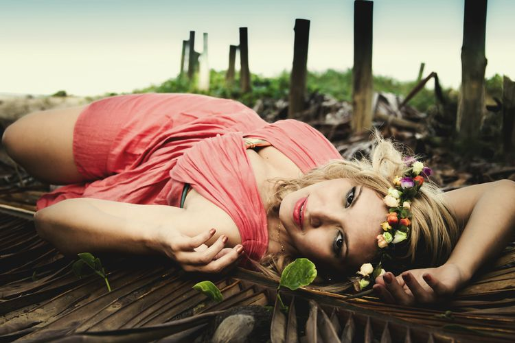 Beautiful Fashion Model Lying On Dry Palm Leaf