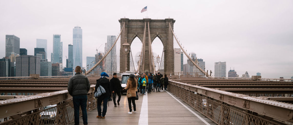 People Walking On Brooklyn Bridge In City