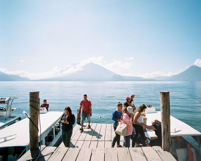 People relaxing on pier over sea against sky