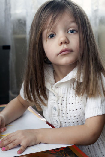 Portrait of cute girl with paper on table sitting at home