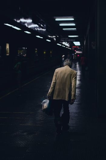 Rear view of man walking on at subway station