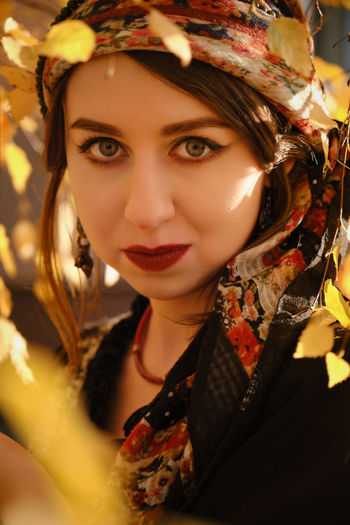 Close-up portrait of young woman amidst leaves