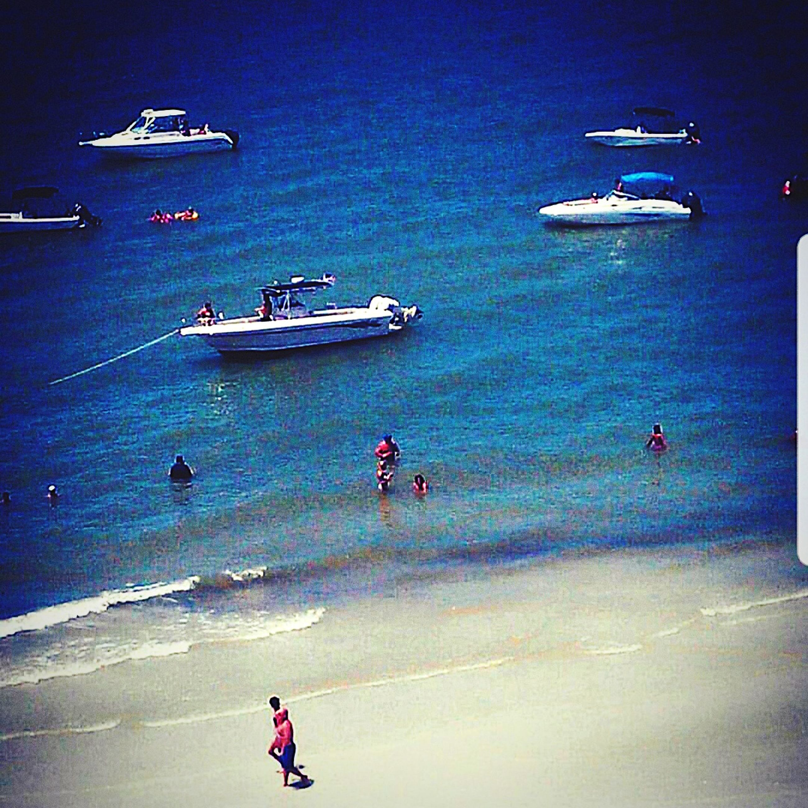 water, nautical vessel, transportation, sea, mode of transportation, high angle view, group of people, real people, nature, beach, men, travel, blue, land, day, people, lifestyles, sky, leisure activity