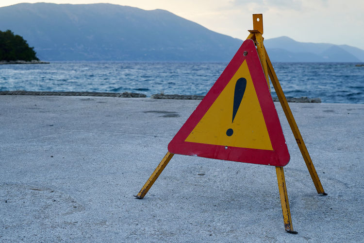 Close-up of warning sign on beach