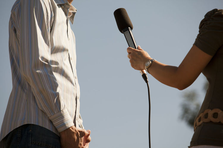 Midsection of reporter taking interview of man against clear sky