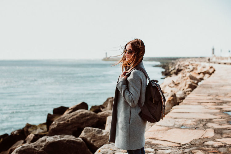 Side view of woman wearing backpack while standing on pier over sea against clear sky