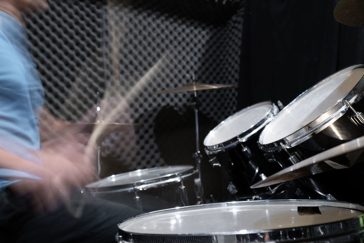 Blurred motion of drummer playing music at concert
