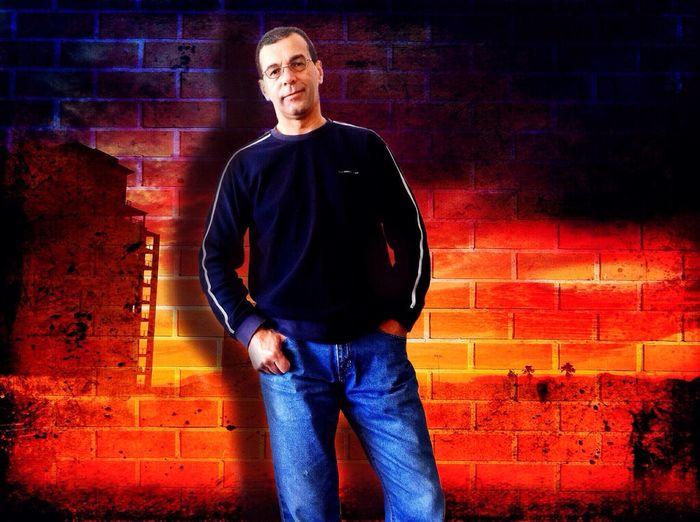 Self Portrait - Age 50 Male Tall Denim Brick Wall Dark Blue Top Reddish Background