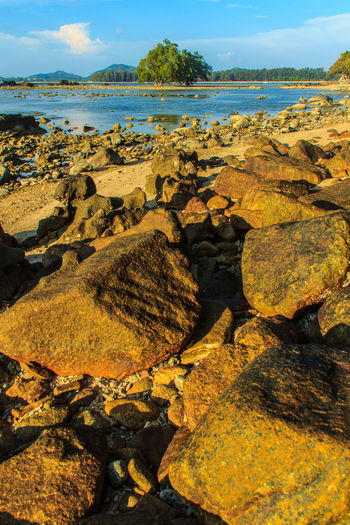 Lonely remote island with rock beach. Beautiful rocky coastline with full of stones on the beach when the sea water receded with dramatic blue sky background on the cloudy day. Coastline Coastline Landscape Coastline Nature Water Lonely Lonely Island Lonely Place  Peaceful View Rock Beach Sea Rocky Beach Rocky Coastline Rocky Shore Beach Beauty In Nature Coastline Sky Day Landscape Lonelyplanet Nature No People Outdoors Peaceful Peaceful Nature Peaceful Place Pebble Beach Rock - Object Rock Beach Rocky Coast Rocky Landscape Scenics Sea Sky Tranquil Scene Tranquility Water