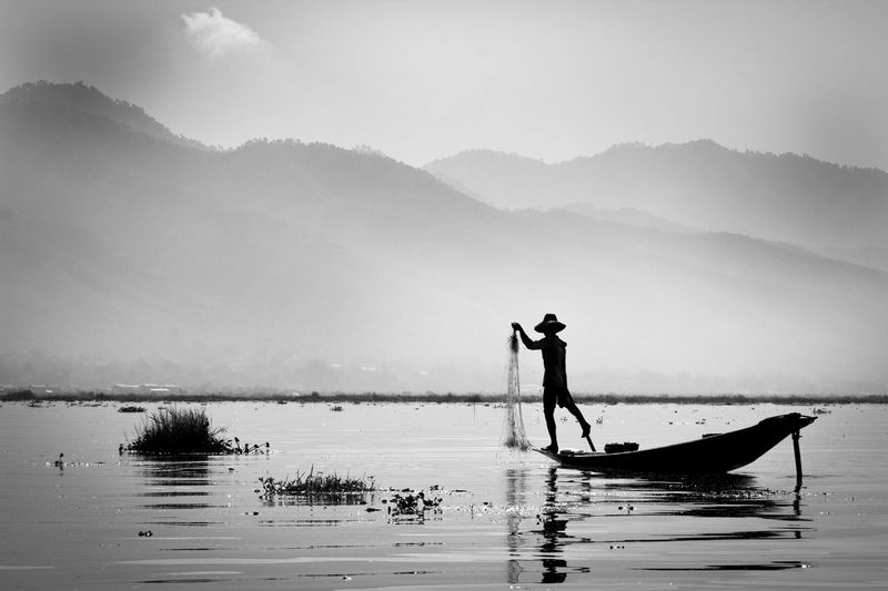 Silhouette fisherman fishing on boat in lake