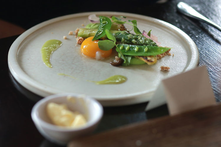 High angle view of egg yolk with vegetables served in plate
