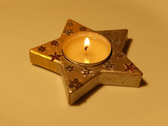 Close-Up Of Star Shape Tea Light Candle Yellow Background