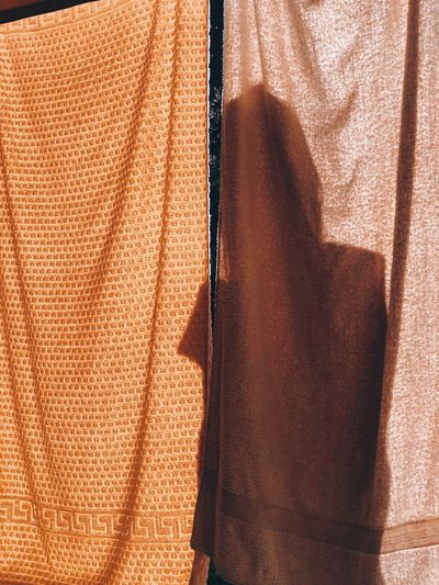 Shadow of a woman behind towels