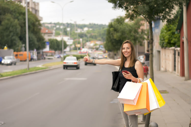 Portrait of woman with shopping bags hitchhiking in city