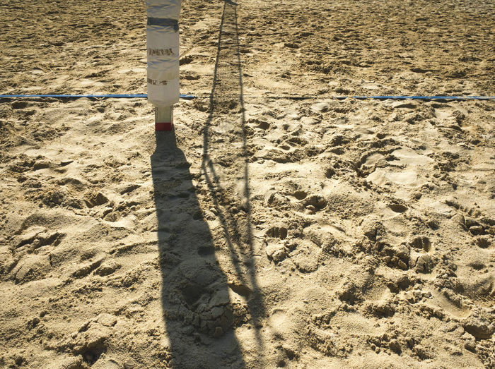 Shadow of volleyball net on sand at beach