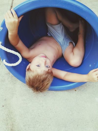 High angle view portrait of boy playing in bowl