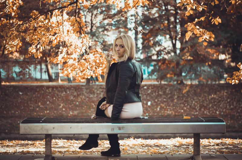 Woman sitting in park during autumn