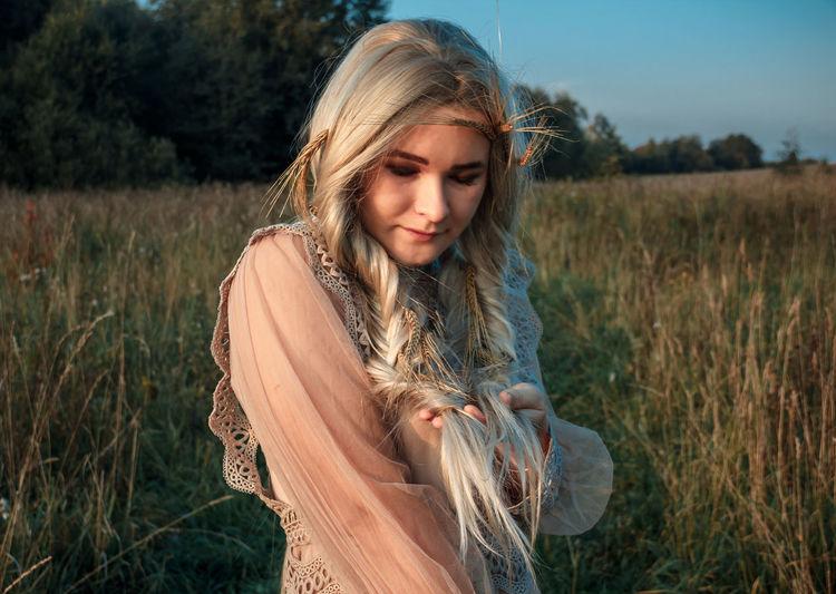Beautiful young woman lying on field