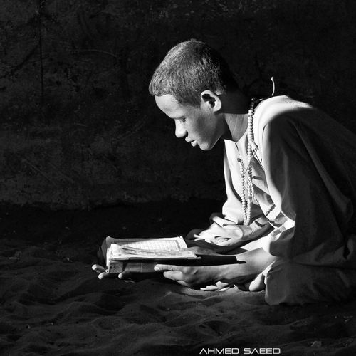 portrait of a child from eastern Sudan reading The Holy Quran under the sun light. Portrait Blackandwhite Beautiful Sunlight Holy Quraan
