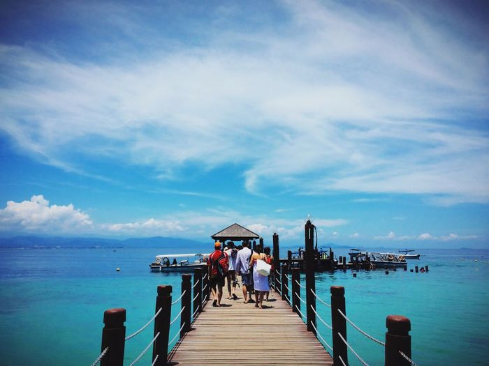 Rear view of people walking on jetty against sea