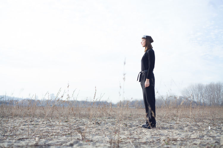 Side view of young woman standing on field against sky