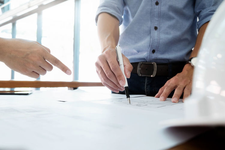 Close-up of architect discussing over blueprint at table in office