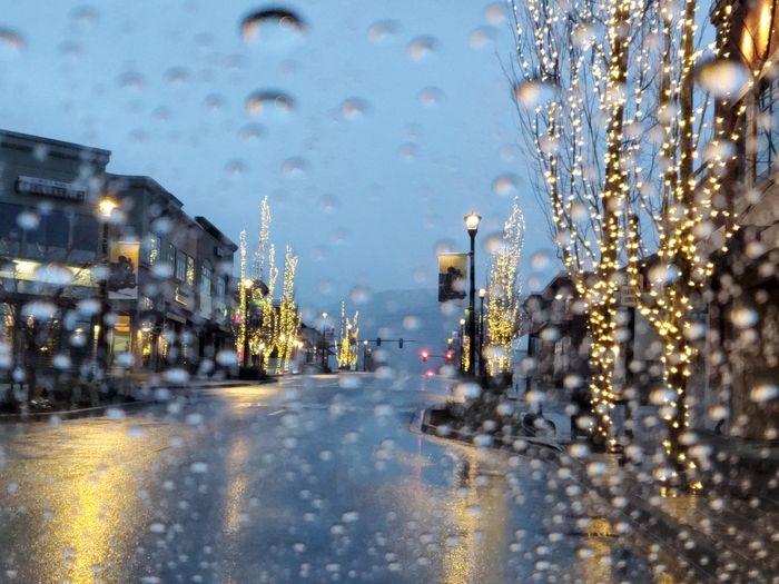 Wet street by illuminated buildings during rainy season