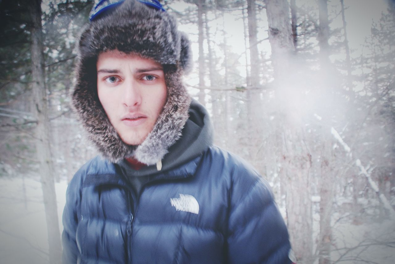 winter, cold temperature, warm clothing, forest, real people, tree, one person, snow, front view, leisure activity, lifestyles, young adult, outdoors, looking at camera, nature, focus on foreground, day, scarf, headshot, portrait, tree trunk, young women, beauty in nature, close-up, people