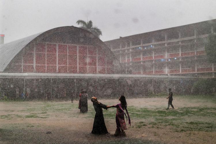 People enjoying rain on field