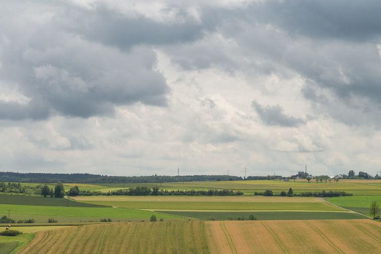 Idyllic shot green landscape against cloudy sky