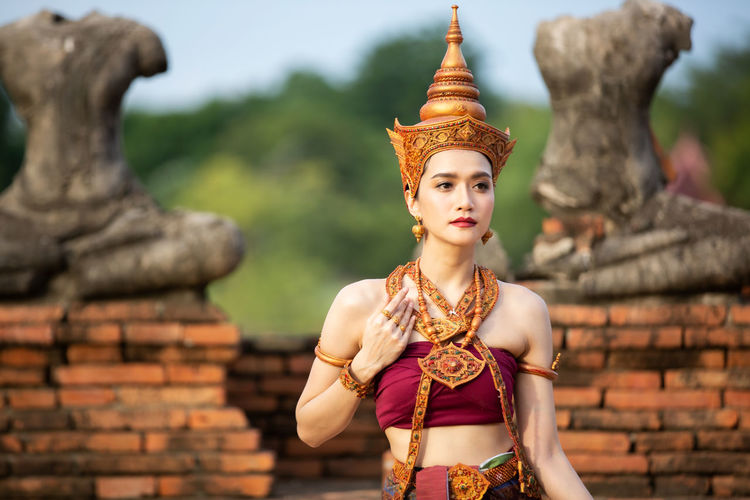 Young woman in traditional clothing standing against built structure