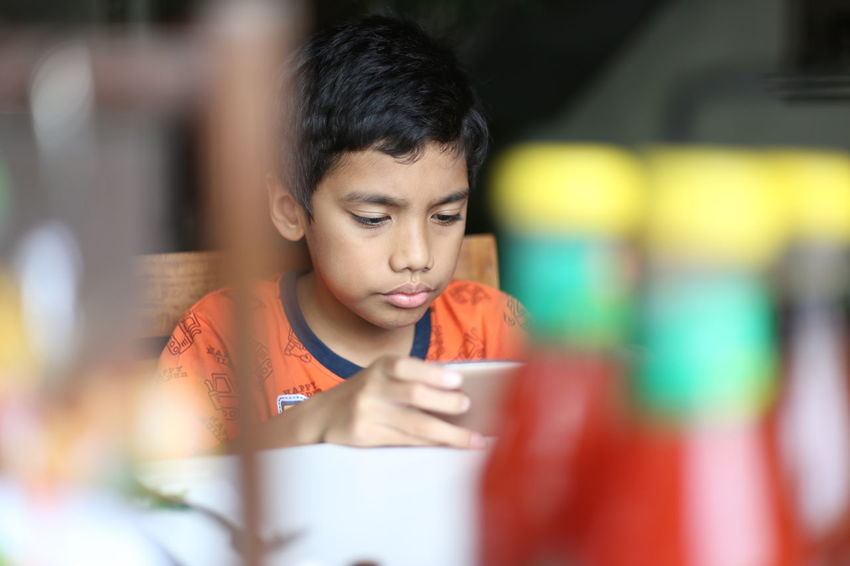 Boys Child Childhood Children Only Color Image Connection Convenience Domestic Life Fun Gamer Horizontal INDONESIA Indoors  Kitchen Lifestyles Looking Males  Mobile Phone One Person Only Photography Playing Smart Phone Video Games